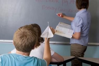 Bilde: Skolegutt kaster papirfly mot læreren.