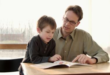 Bilde av et barn og en ung mann som leser.