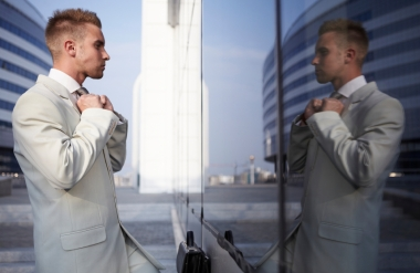 Bilde av ung mann i dress som speiler seg i glassvegg
