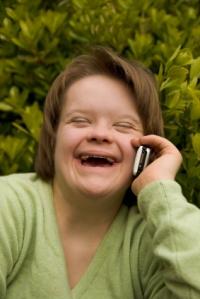 jente med Downs syndrom som snakker i telefon og ler.