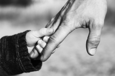 Barn som leier en mann. Barnehånd i mannehånd
