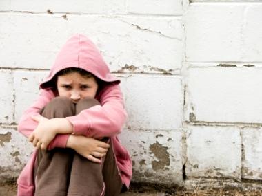 Redd jente som sitter på bakken inntil en vegg. Ill.foto: Blue_Cutler, iStockphoto