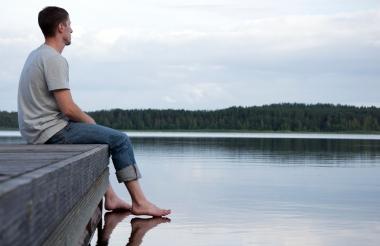 Ung mann som sitter på brygga og ser utover stille vann.