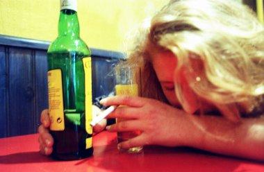 deprimert kvinne med whiskyflaske