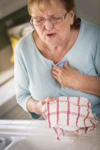 Grimacing Senior Adult Woman At Kitchen Sink With Chest Pains.