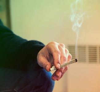 Hånd som holder en joint.
