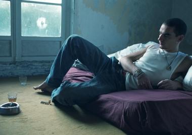Ung mann på madrass med røyk og glass