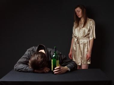 Full mann lent over bordet, kvinne står bak