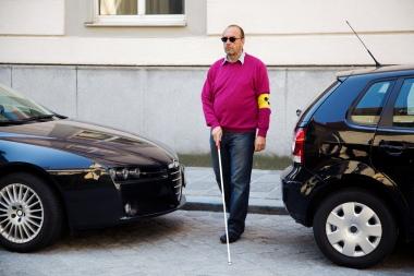Blind mann med stokk krysser vei mellom biler