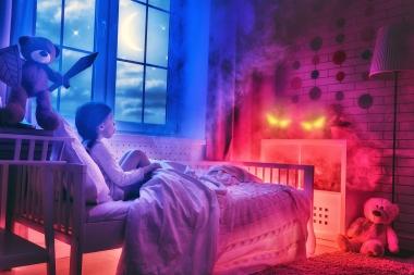 Barn som sitter i senga, skummel stemning
