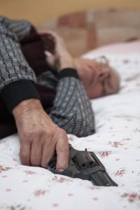 eldre mann med revolver i senga