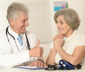 Mannlig lege med eldre kvinnelig pasient.
