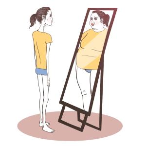 jente med anoreksi som ser seg i speilet