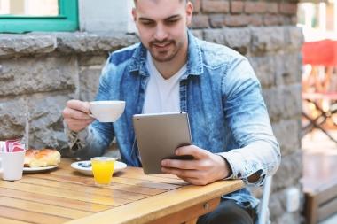 ung mann som leser på kafé