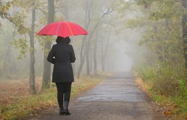 Kvinne som går i regnet med paraply