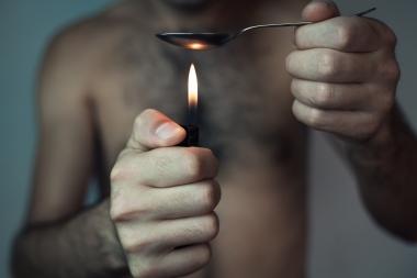 Rusmisbruker gjør klar heroin i en skje