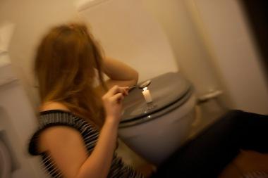 Narkoman kvinne som varmer narkotika på toalett.