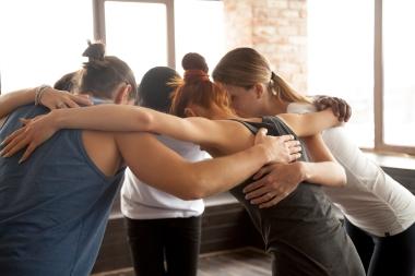 gruppe ungdom som holder rundt hverandres skuldre