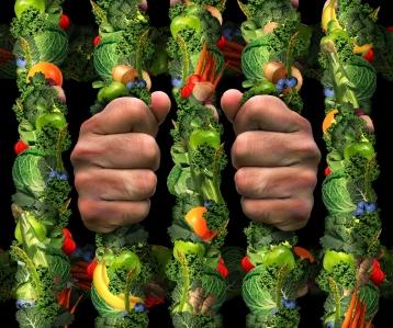 Hender som tar rundt et gitter av grønnsaker.