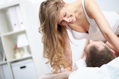 Ung kvinne over mann i seng
