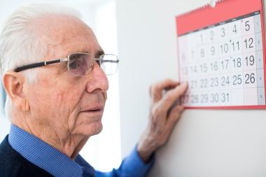 forvirret eldre mann som ser på kalender
