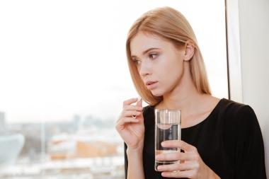 ung trist kvinne som tar tablett