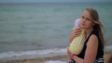 trist mor med baby ved sjøen