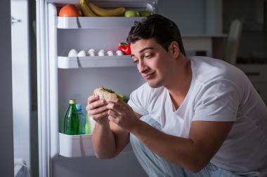 mann som spiser fra åpent kjøleskap