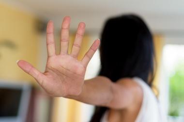 Kvinne som holder opp en hånd for å verge seg