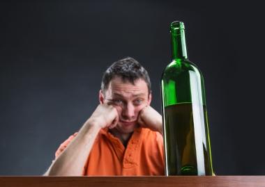 Trist mann som ser på vinflaske