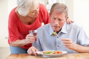 eldre par der kvinnen hjelper mannen å spise