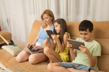 mor og barn i sofaen med pc og nettbrett