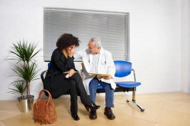 mannlig lege som trøster kvinnelig pasient