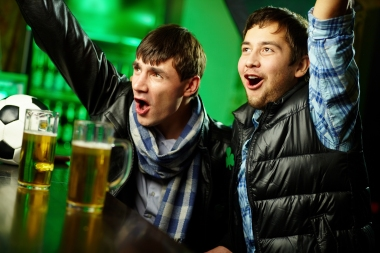 to unge menn som drikker øl på pub.