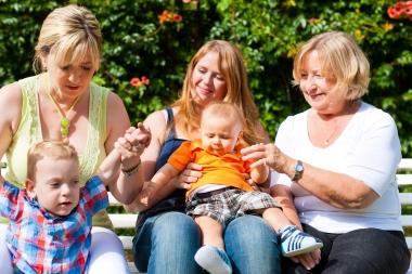 To søstre, bestemor og småbarn på benk i parken