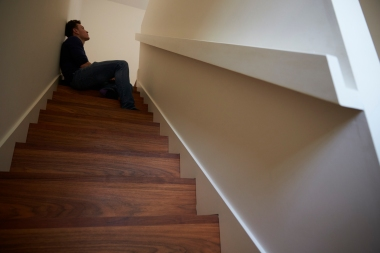 deprimert ung mann som sitter i trappen hjemme
