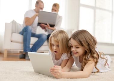 foreldre og barn med nettbrett og pc
