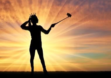 person som tar selfie med solnedgang som bakgrunn
