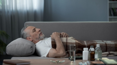 eldre mann som sover på sofa med medisiner på salongbordet