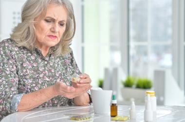 Eldre kvinne som tar tabletter