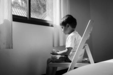 ensomt barn som sitter i en stol ved vinduet