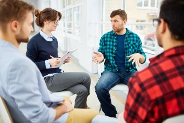 voksne som sitter på stoler og snakker sammen