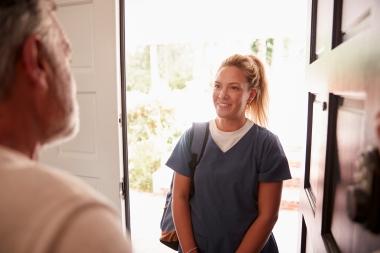 ung kvinne og eldre mann møtes i døråpning