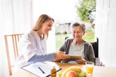 pleier og eldre kvinnelig pasient ved bord, med nettbrett