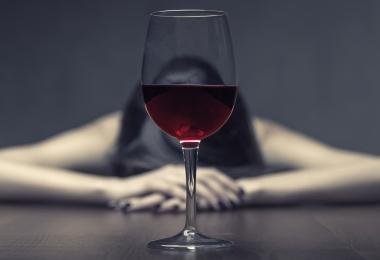 rødvinsglass med kvinne i bakgrunnen