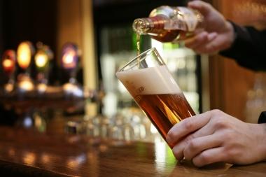 mann som skjenker øl i et glass