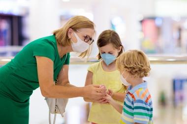 mor og barn med ansiktsmasker spritvasker hendene