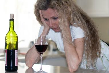 trist kvinne som drikker rødvin alene