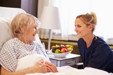 sykepleier som snakker med sengeliggende eldre pasient