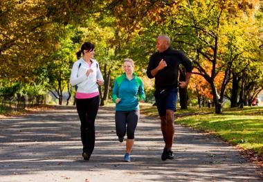 tre personer som løper i parken